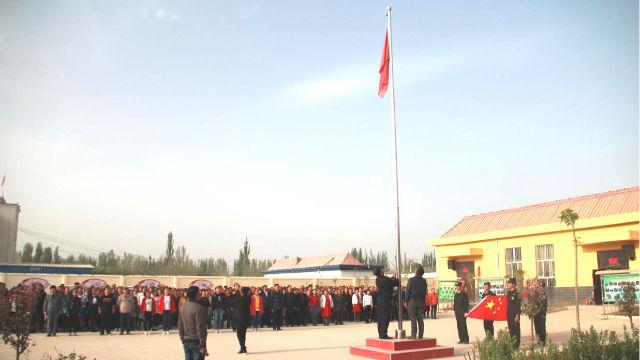 Les habitants d'une localité du Xinjiang sont organisés par le gouvernement pour hisser le drapeau national.