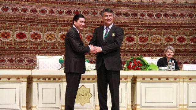 Tashpolat Tiyip en train de recevoir le Prix international Magtymguly des mains du président du Turkmenistan, Gurbanguly Berdimuhamedow (à gauche).