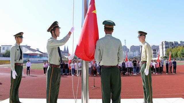 Des élèves du Xinjiang du lycée de Kou'an à Jiangsu participent à une cérémonie de lever de drapeau.