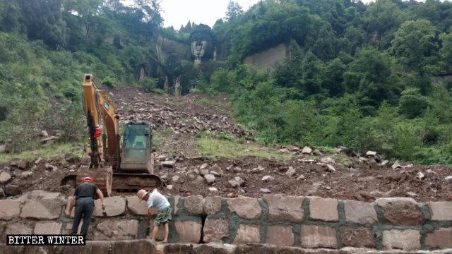 Des ouvriers du bâtiment construisent un mur de soutènement alors qu'ils se préparent à couvrir la statue de Bouddha.