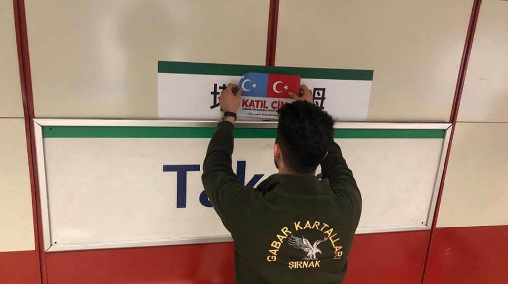 Un sympathisant turc de la cause ouïghoure couvre le panneau stop en mandarin du tramway Taksim avec les drapeaux du Turkestan oriental et de la Turquie et les mots katil çin qui signifient « Chinois assassin ! ».